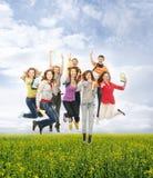Un gruppo di adolescenti felici che saltano sull'erba Fotografie Stock Libere da Diritti
