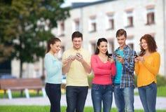 Gruppo di adolescenti sorridenti con gli smartphones Fotografia Stock