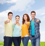Gruppo di adolescenti sorridenti sopra cielo blu ed erba Fotografia Stock