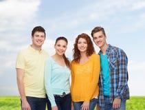 Gruppo di adolescenti sorridenti sopra cielo blu ed erba Fotografie Stock Libere da Diritti