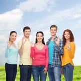 Gruppo di adolescenti sorridenti sopra cielo blu ed erba Immagine Stock