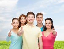 Gruppo di adolescenti sorridenti sopra cielo blu ed erba Immagini Stock Libere da Diritti