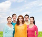 Gruppo di adolescenti sorridenti sopra cielo blu ed erba Immagini Stock