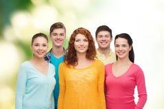 Gruppo di adolescenti sorridenti sopra fondo verde Immagini Stock
