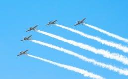 Gruppo di aerei bianchi del turbopropulsore con una traccia di fumo bianco contro un cielo blu Immagini Stock Libere da Diritti