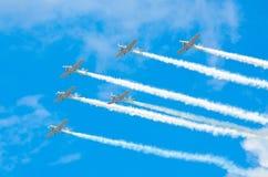 Gruppo di aerei bianchi del turbopropulsore con una traccia di fumo bianco contro un cielo blu Fotografie Stock Libere da Diritti