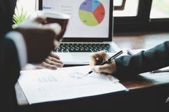 Gruppo di affari che analizza i grafici ed i grafici di reddito con il computer portatile moderno immagine stock