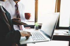 Gruppo di affari che analizza i grafici ed i grafici di reddito con il computer portatile moderno fotografia stock