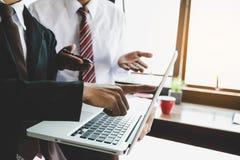 Gruppo di affari che analizza i grafici ed i grafici di reddito con il computer portatile moderno immagini stock libere da diritti