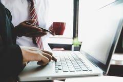 Gruppo di affari che analizza i grafici ed i grafici di reddito con il computer portatile moderno fotografia stock libera da diritti