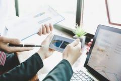 Gruppo di affari che analizza i grafici ed i grafici di reddito sullo smartphone immagine stock libera da diritti