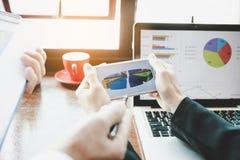 Gruppo di affari che analizza i grafici ed i grafici di reddito sullo smartphone fotografie stock libere da diritti