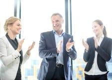 Gruppo di affari che applaude e che sorride Fotografia Stock