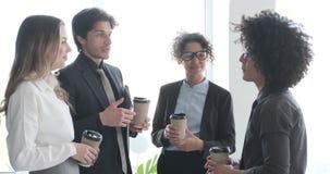 Gruppo di affari che discute mentre mangiando caffè in ufficio video d archivio