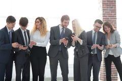 Gruppo di affari che guarda allo smartphone in ufficio Immagine Stock