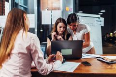 Gruppo di affari che lavora insieme studiando i grafici ed i diagrammi facendo uso del computer portatile in ufficio moderno fotografie stock