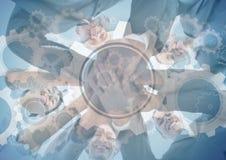 Gruppo di affari che mette le mani insieme alla sovrapposizione grafica dell'ingranaggio Fotografia Stock Libera da Diritti