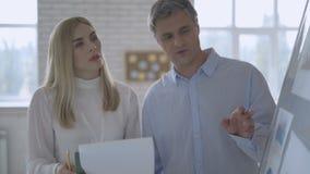 Gruppo di affari che parla del grafico sulla lavagna nella sala riunioni 4K video d archivio