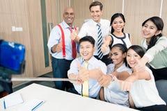 Gruppo di affari che prende immagine con il bastone del selfie Fotografie Stock Libere da Diritti