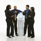 Gruppo di affari che si leva in piedi intorno al dispositivo di raffreddamento di acqua. Fotografia Stock Libera da Diritti