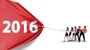 Gruppo di affari che tira bandiera con i numeri 2016 Fotografia Stock