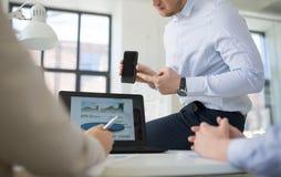 Gruppo di affari con funzionamento dello smartphone all'ufficio fotografie stock libere da diritti