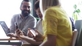 Gruppo di affari con gli smartphones ed il pc della compressa video d archivio