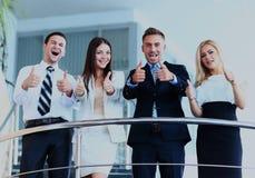 Gruppo di affari con i pollici su in scale Immagine Stock