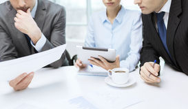 Gruppo di affari con il grafico, il pc della compressa ed il caffè Fotografie Stock