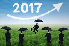 Gruppo di affari con l'ombrello nel prato Fotografia Stock Libera da Diritti