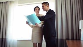 Gruppo di affari con le carte che lavorano alla camera di albergo stock footage