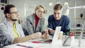 Gruppo di affari dei giovani disciplinati che godono del lavoro insieme, gruppo di millennials che parla divertendosi nell'uffici video d archivio