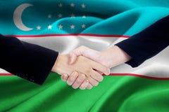 Gruppo di affari di due mani con la bandiera dell'Uzbekistan Fotografie Stock Libere da Diritti
