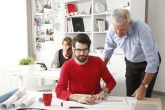 Gruppo di affari nel piccolo studio dell'architetto Immagini Stock