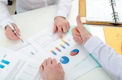 Gruppo di affari soddisfatto circa i risultati finanziari Fotografia Stock