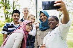 Gruppo di allievi che per mezzo del telefono mobile Fotografia Stock Libera da Diritti