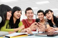 Gruppo di allievi che per mezzo del telefono mobile Fotografie Stock Libere da Diritti