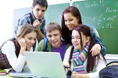 Gruppo di allievi che studiano con il computer portatile Fotografia Stock Libera da Diritti