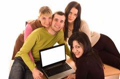 Gruppo di allievi con il computer portatile su bianco Immagine Stock