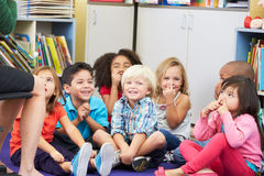 Gruppo di allievi elementari nei nasi commoventi dell'aula Immagini Stock Libere da Diritti