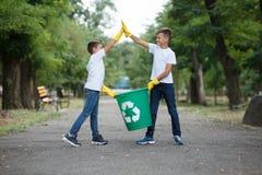 Gruppo di ambiente di carità della raccolta dei rifiuti di aiuto del volontario dei bambini, fuoco molle selettivo Team il lavoro Fotografie Stock Libere da Diritti