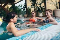 Gruppo di amiche divertendosi nella piscina dell'interno nel centro della stazione termale immagini stock libere da diritti