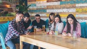 Gruppo di amici al pub che si trascurano a favore del telefono cellulare immagini stock libere da diritti