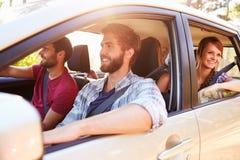 Gruppo di amici in automobile sul viaggio stradale insieme fotografia stock