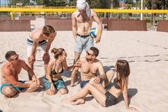 Gruppo di amici caucasici che riposano all'intervallo fra gli insiemi sulla corte della spiaggia immagine stock libera da diritti