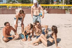 Gruppo di amici caucasici che riposano all'intervallo fra gli insiemi sulla corte della spiaggia immagine stock