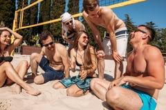 Gruppo di amici caucasici che riposano all'intervallo fra gli insiemi sulla corte della spiaggia fotografie stock libere da diritti