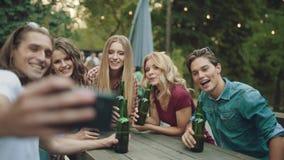 Gruppo di amici che bevono birra e che prendono le foto sul telefono stock footage