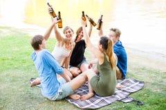 Gruppo di amici che bevono birra nel lago Fotografia Stock