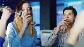 Gruppo di amici che bevono vino in un ristorante o in un caffè, vetri del tintinnio Emozioni positive e un buon tempo stock footage